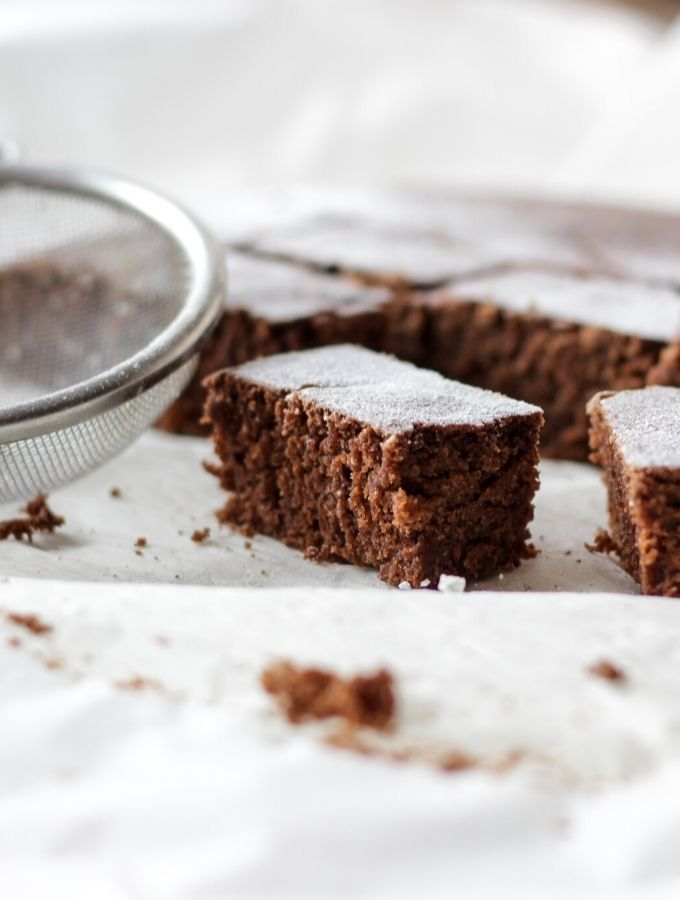 Brownies and sifter on parchment paper