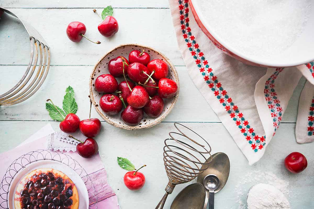 Bowl of cherries surrounded by cooking utensils