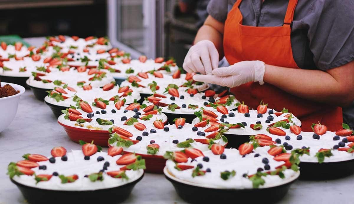 Chef decorating pies with fresh fruit