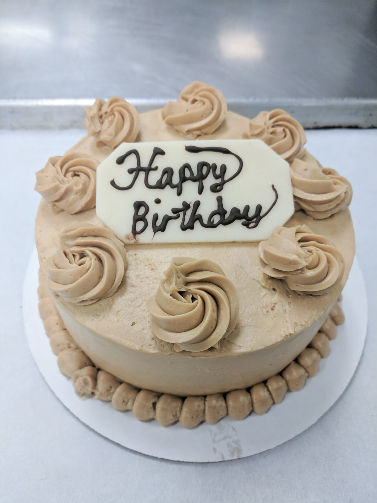 "Genoise cake with coffee buttercream and a marzipan plaque that reads ""Happy Birthday"""
