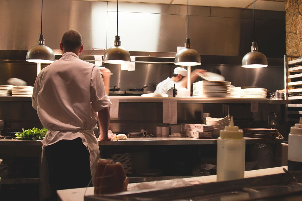 Various cooks standing on the line in a restaurant kitchen