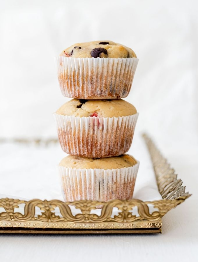 Stack of strawberry chocolate chip muffins on top of a gold tray