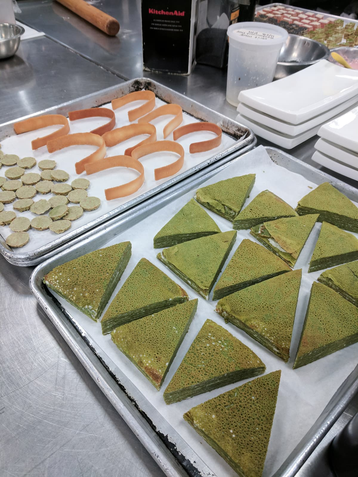 Slices of crepe cake and tuile laid on sheet trays