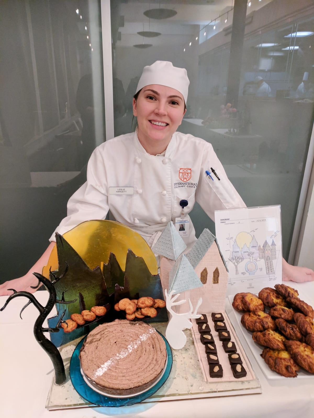 Girl in chef's uniform standing in front of showpiece