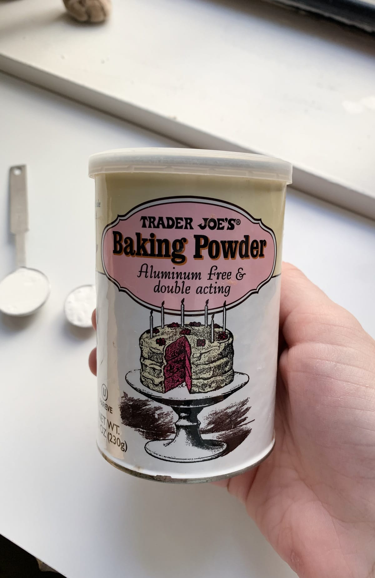 Hand holding a container of baking powder