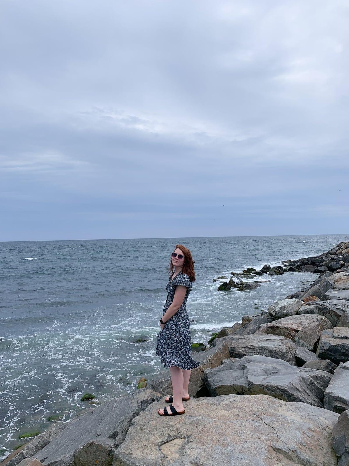 Girl standing on top of rocks next to crashing ocean waves