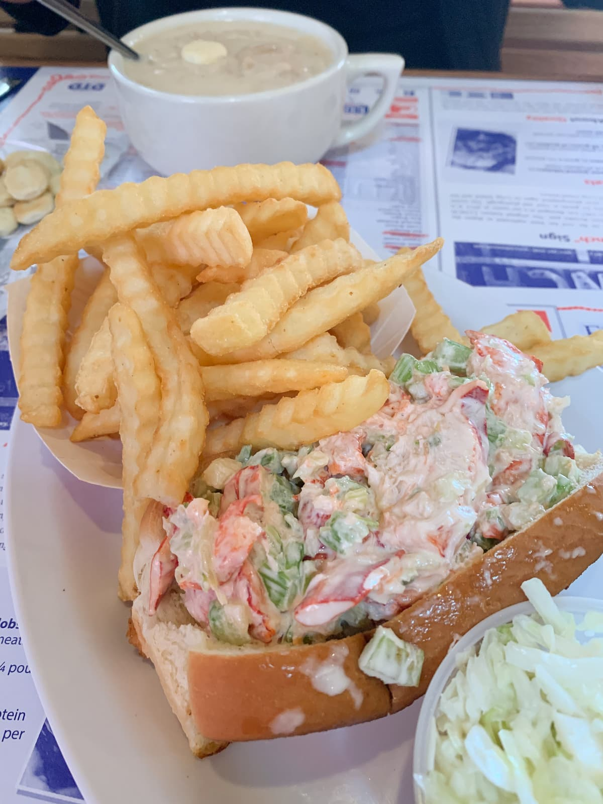 Lobster roll next to lots of crinkly fries