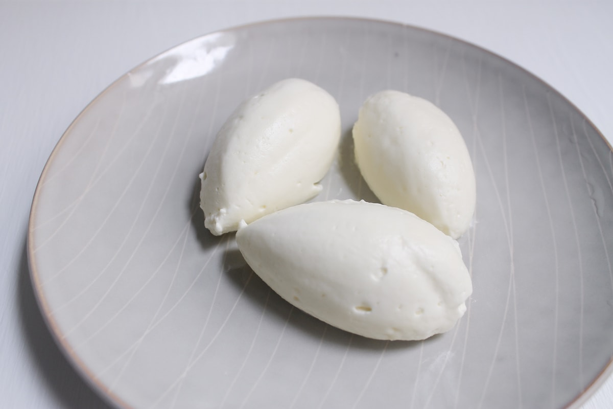 Close-up shot of three quenelles of whipped cream on a plate