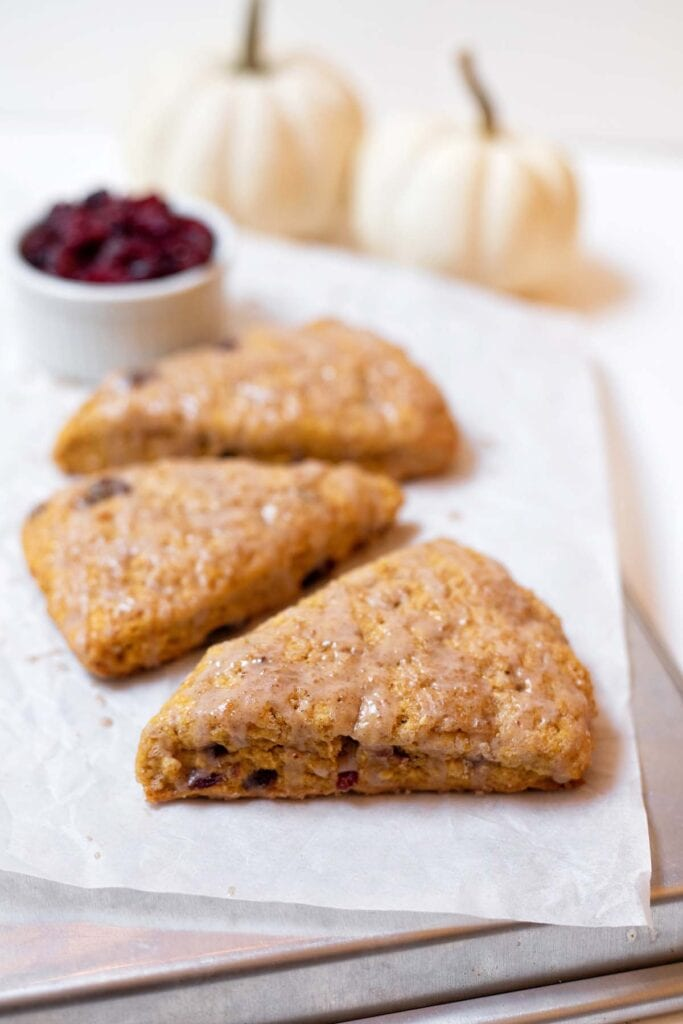 Three pumpkin cranberry scones in a row on parchment paper