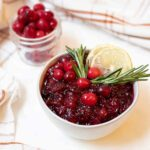 Bowl of cranberry sauce topped with rosemary and lemon