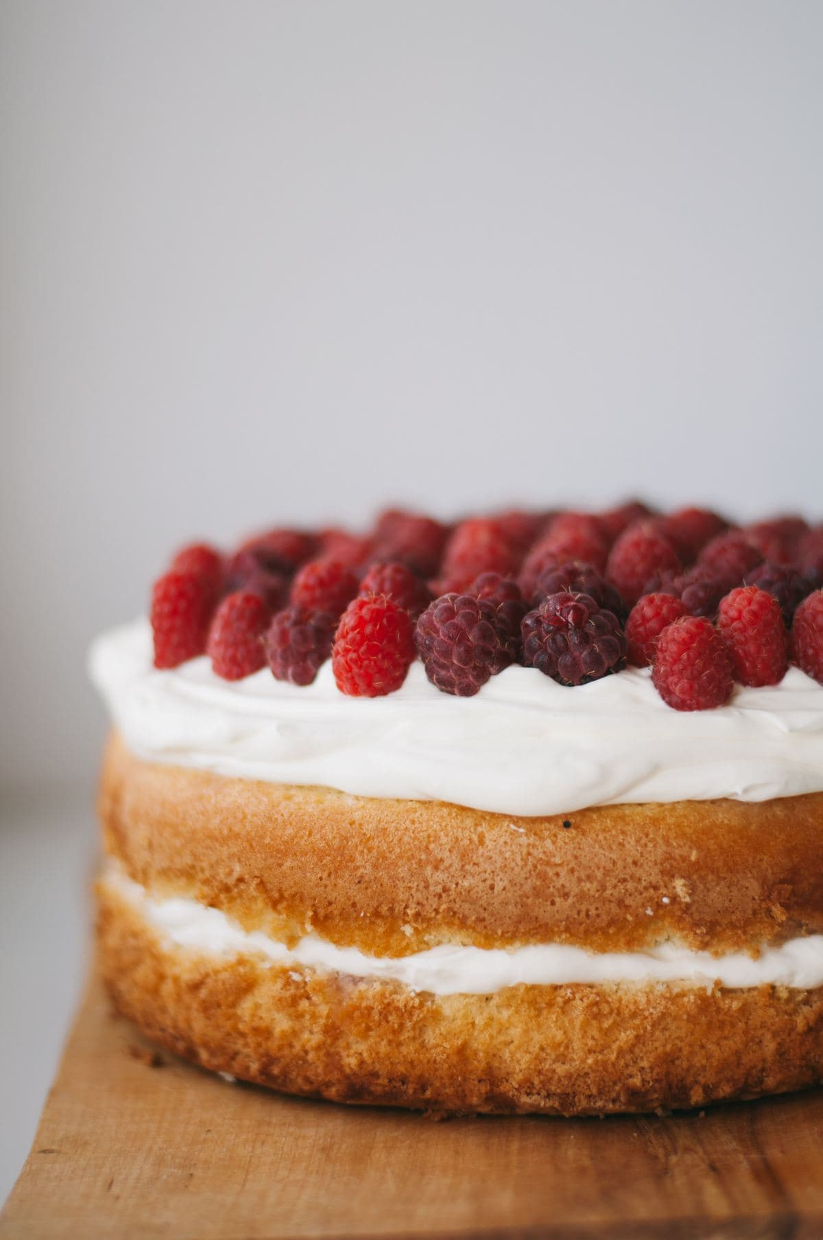 Sandwich cake topped with whipped cream and raspberries