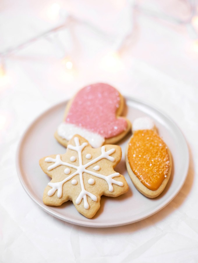 Three Christmas cookies on a plate: an orange light, a pink mitt, and a white snowflake