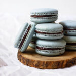 Stack of earl grey macarons on top of a wooden coaster