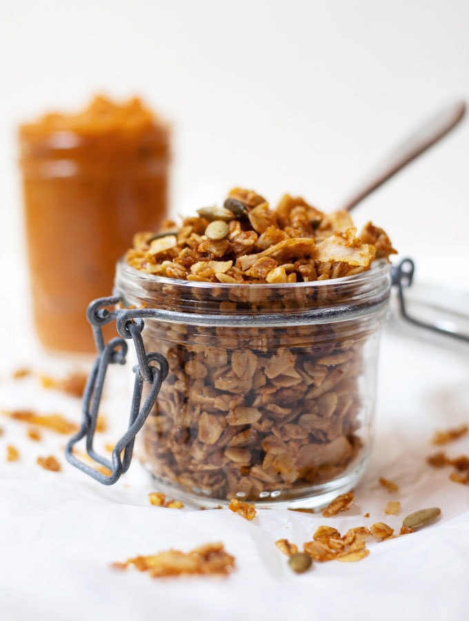 A canister of pumpkin granola with a jar of pumpkin in the background