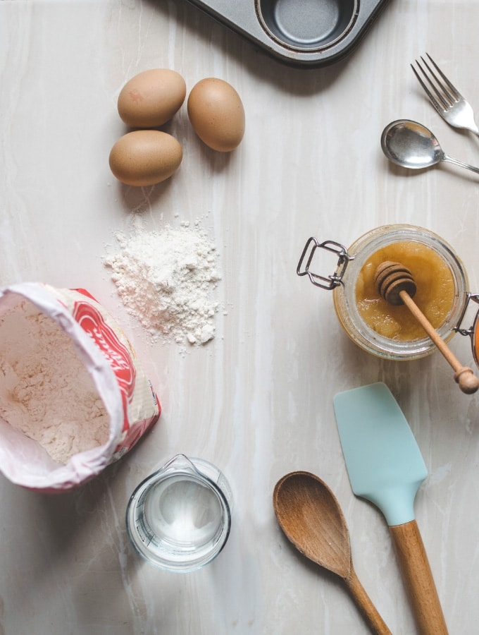 Flatlay of various baking items, including flour, eggs, and honey
