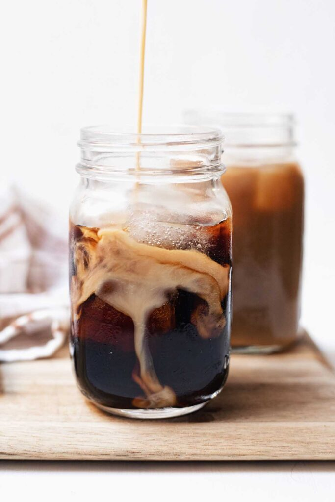 Two glasses of cold brew with pumpkin cream being poured in