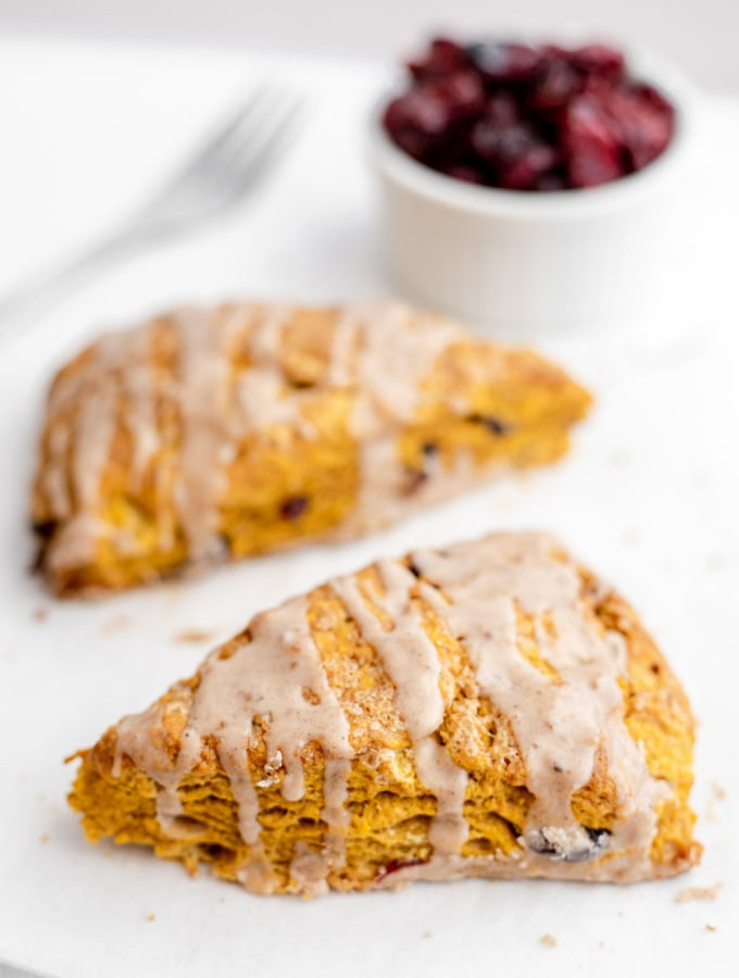 Two pumpkin cranberry scones in front of a bowl of dried cranberries