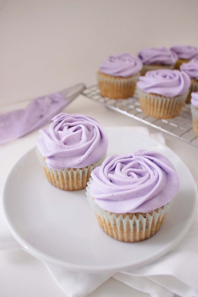 Two earl grey and lavender cupcakes on a plate with several others behind them