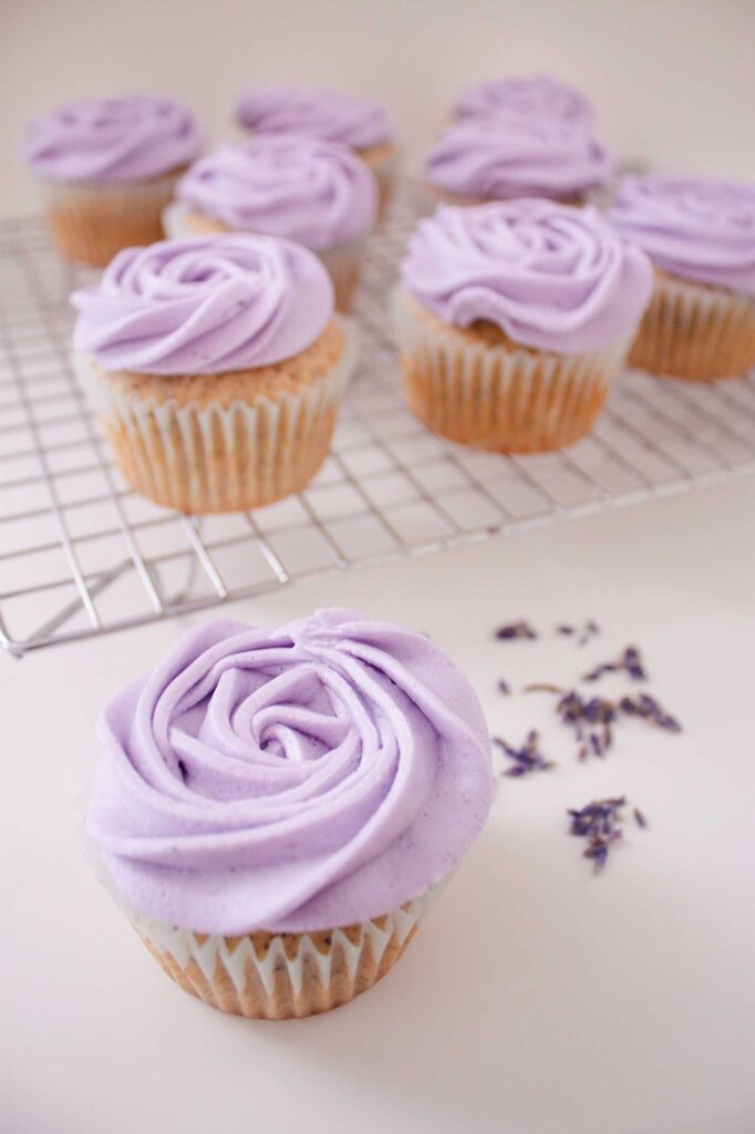 Earl grey and lavender cupcake with lavender sprinkled behind it