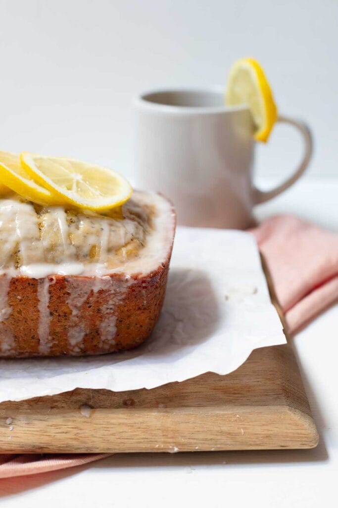 Earl grey and lemon loaf cake resting on a cutting board with a mug of tea behind it