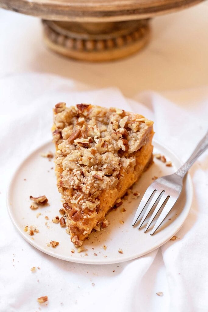 Slice of sweet potato casserole cheesecake on a plate with a fork next to it
