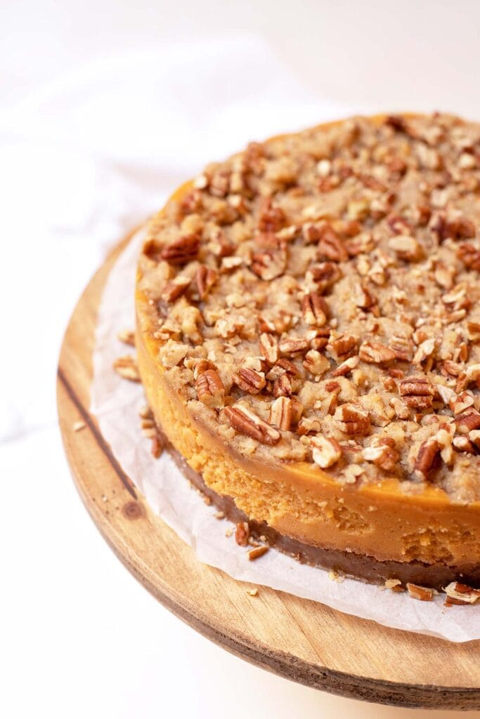 Uncut sweet potato casserole cheesecake on top of a cake stand