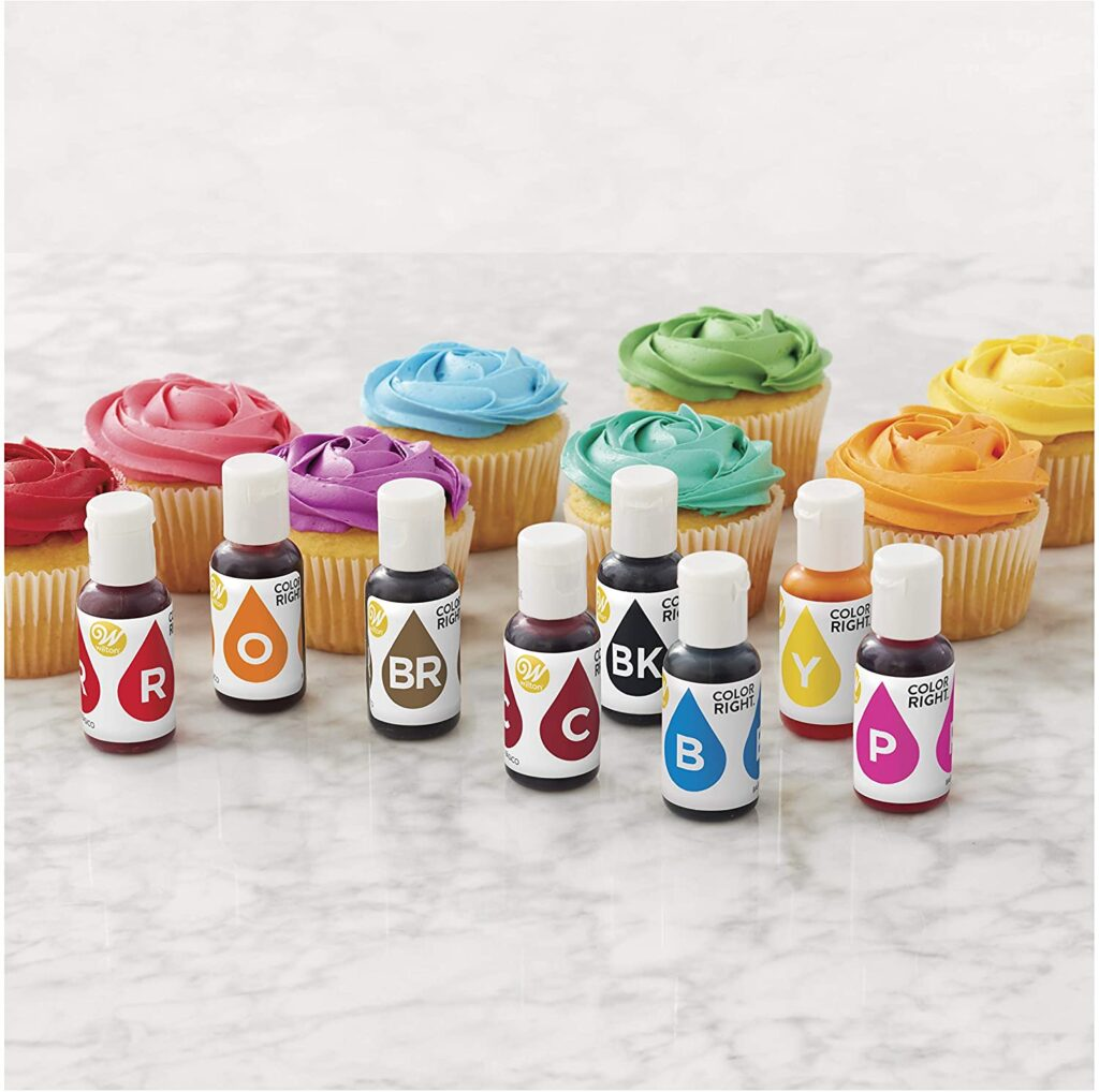 Wilton food coloring set in front of different colored cupcakes