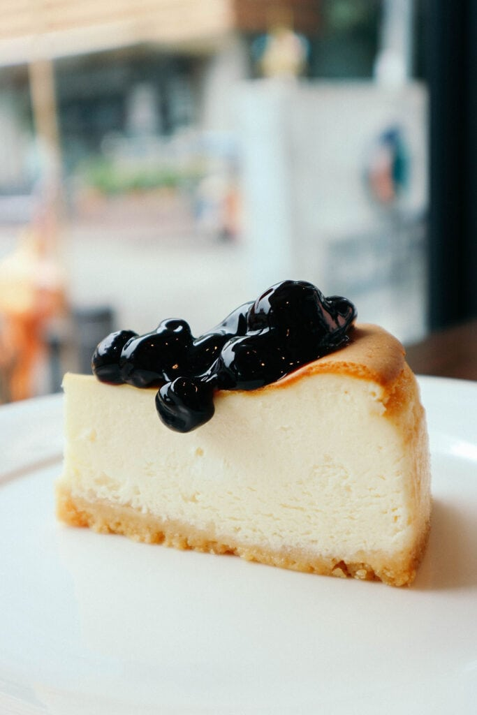 Slice of blueberry cheesecake in front of a window