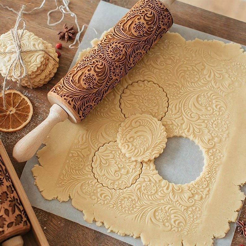 Engraved rolling pin next to cookie dough that has been cut out