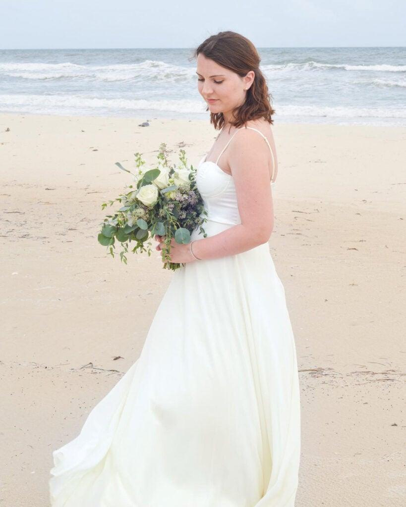 Leslie Jeon in wedding dress holding bouquet on beach
