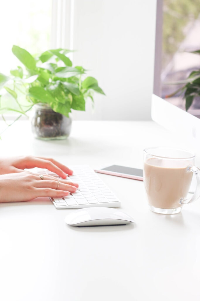 Hands typing at a computer next to a cup of coffee and a plant