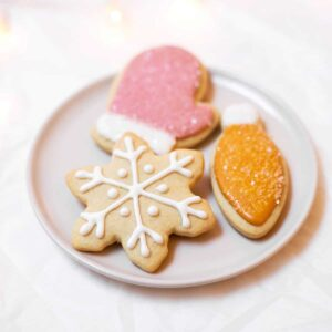 A plate of Christmas cookies: one mitten, one snowflake, and one light