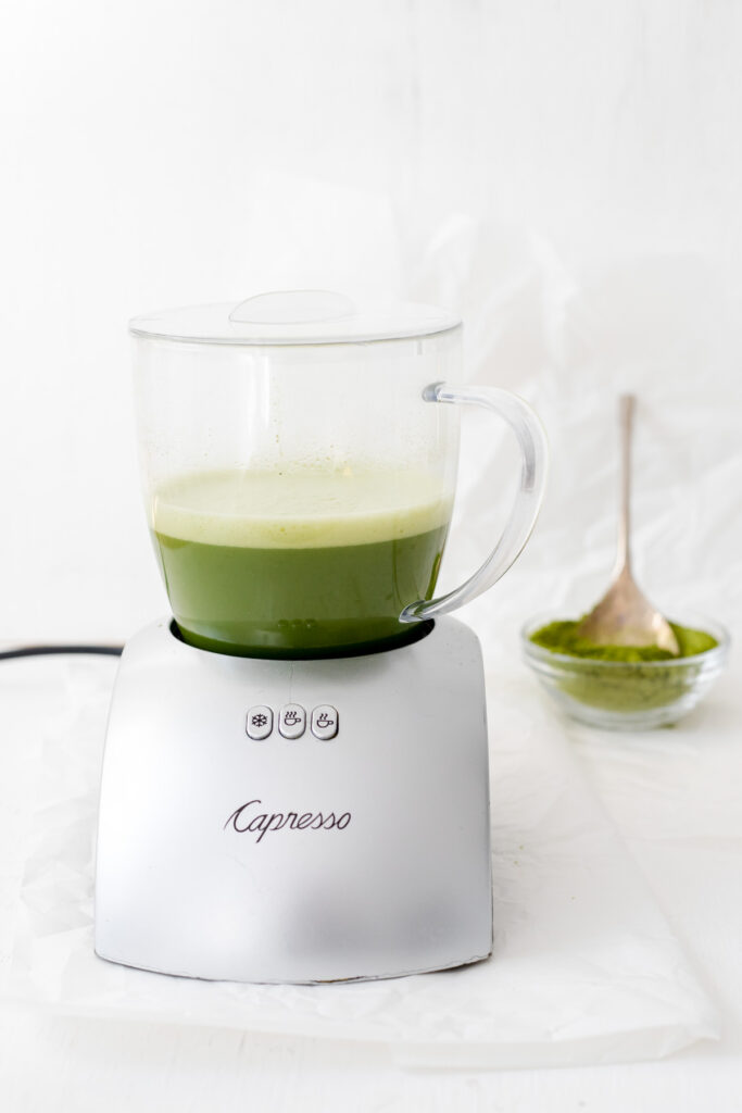 Milk frother with a matcha latte and a bowl of matcha powder with a spoon