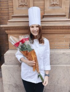 Leslie Jeon in chef's whites and hat holding roses