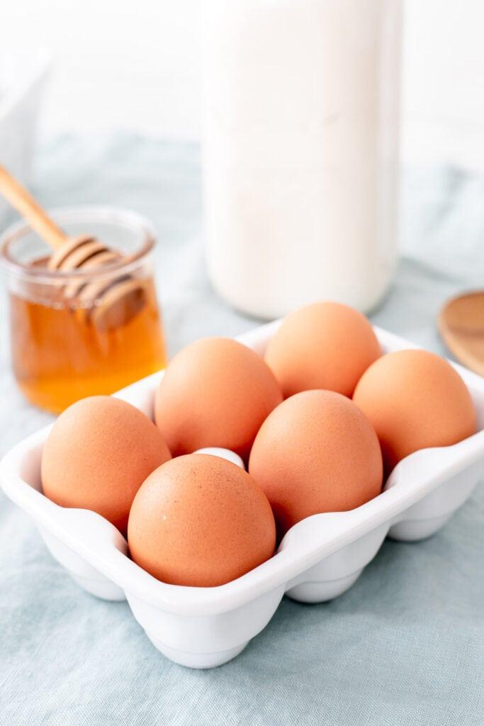 Carton of eggs, a pot of honey, a milk jug, and a wooden spoon