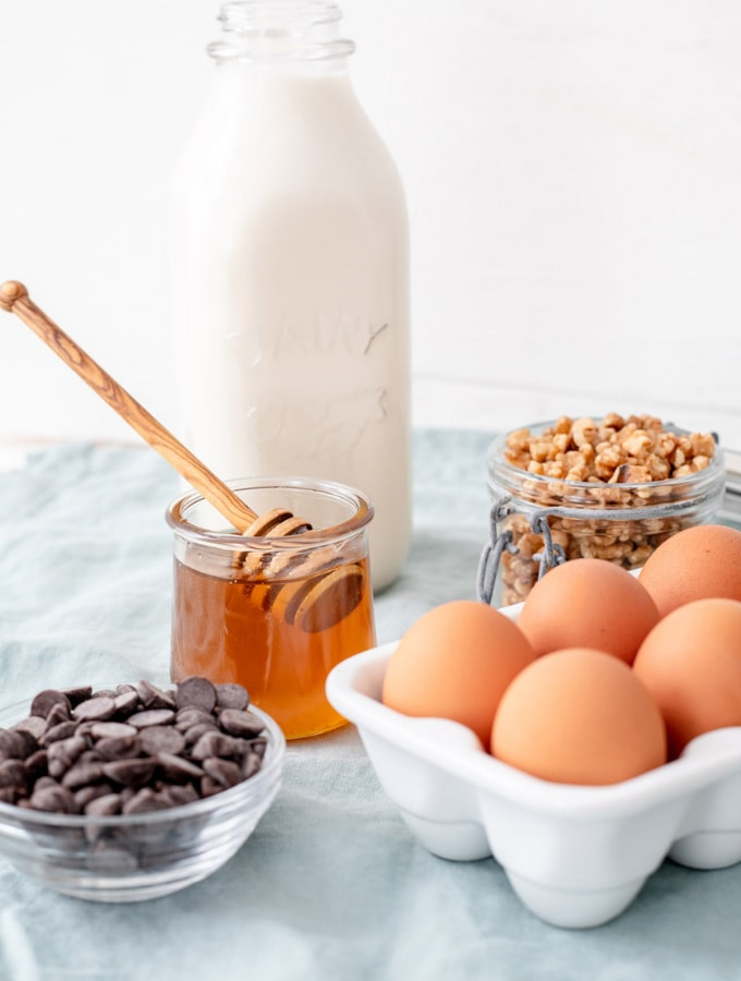 Various baking ingredients like eggs, honey, milk, and chocolate chips
