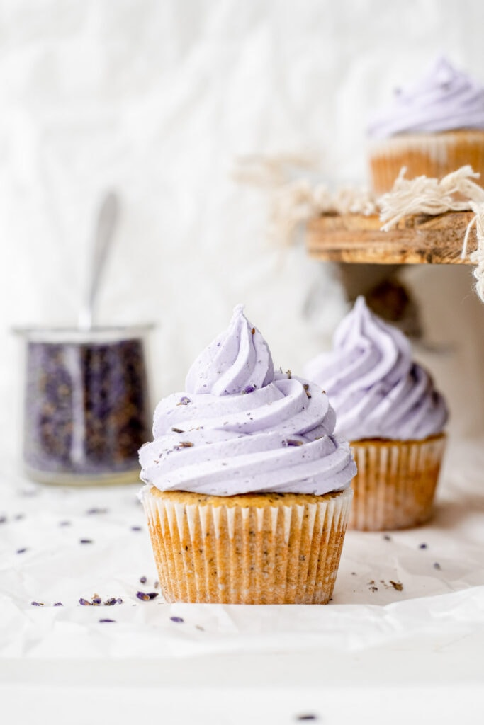 Two earl grey lavender cupcakes in front of a container of lavender