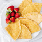 Overhead shot of crepes on a plate with strawberries and a bowl of whipped ricotta