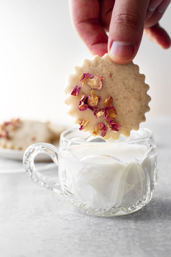 Hand dunking rose cardamom shortbread cookie into a cup of milk