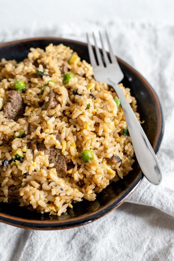Bowl of beef fried rice with a fork resting on top