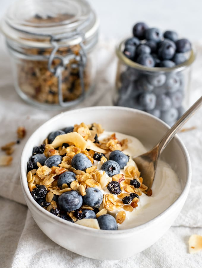 Bowl of yogurt with blueberry granola and blueberries on top
