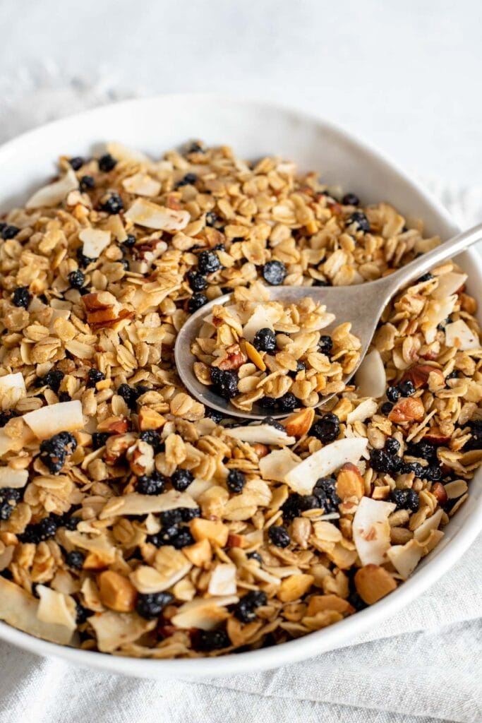 Large bowl of homemade blueberry granola with a spoon resting on top