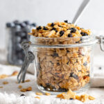 Mason jar of blueberry granola in front of a cup of blueberries