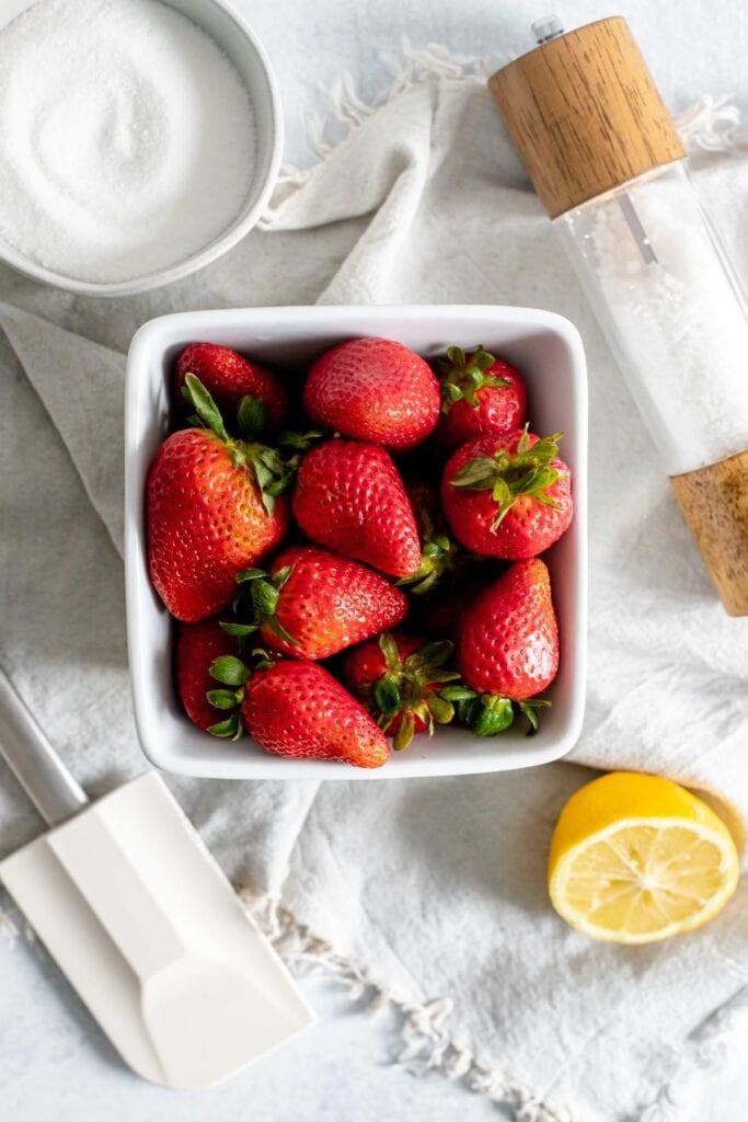 Overhead shot of basket of strawberries, lemon, spatula, salt shaker, and bowl of sugar