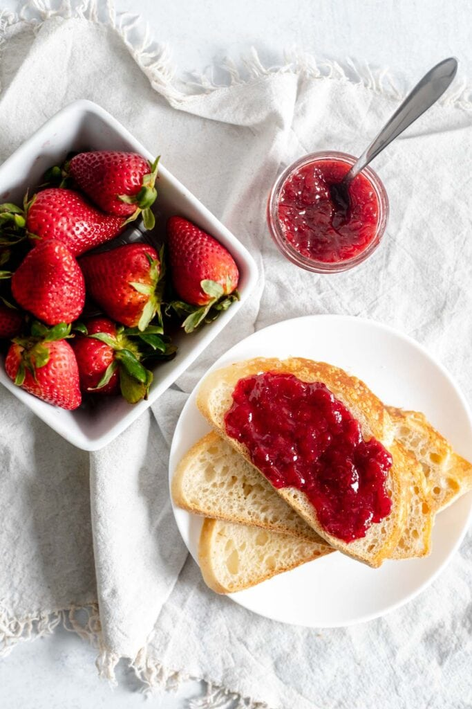 Overhead shot of basket of strawberries, bread with strawberry jam, and jam in a jar