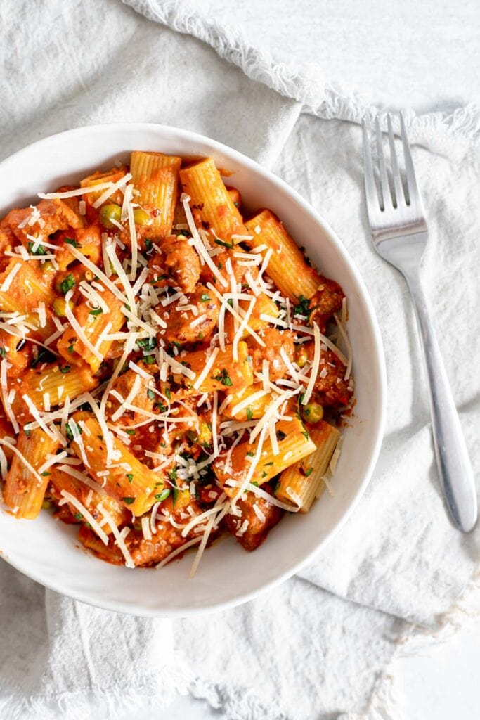 Overhead shot of rigatoni with sausage and peas in a bowl next to a fork