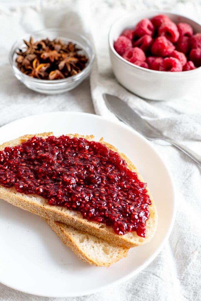 Toast with raspberry jam in front of a bowl of star anise and a bowl of raspberries