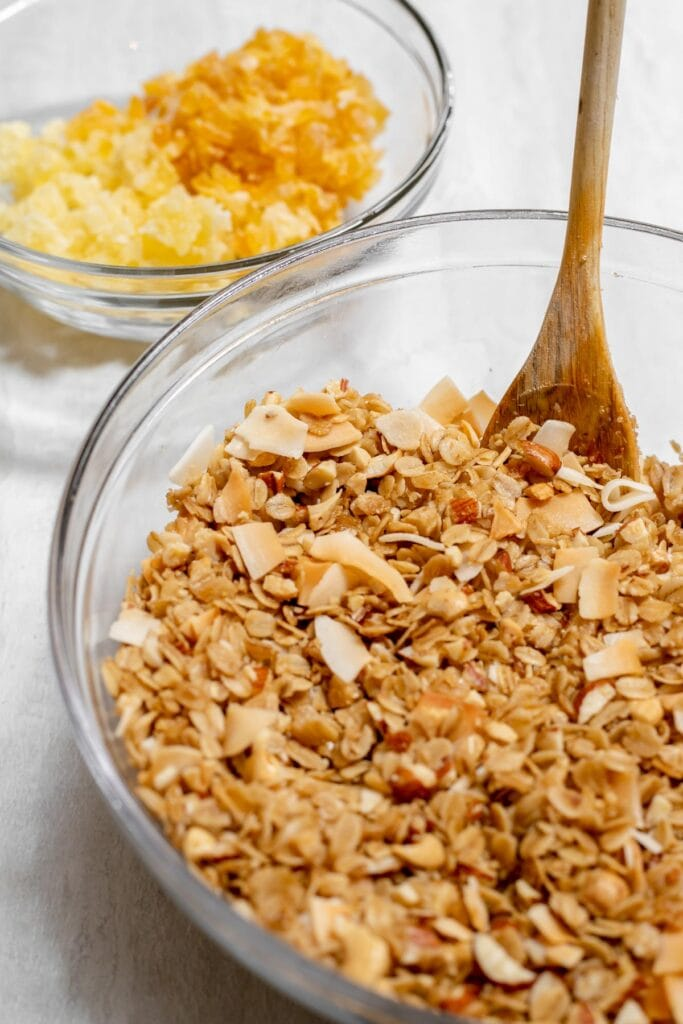 Bowl of granola with wooden spoon next to a bowl with dried mango and dried pineapple