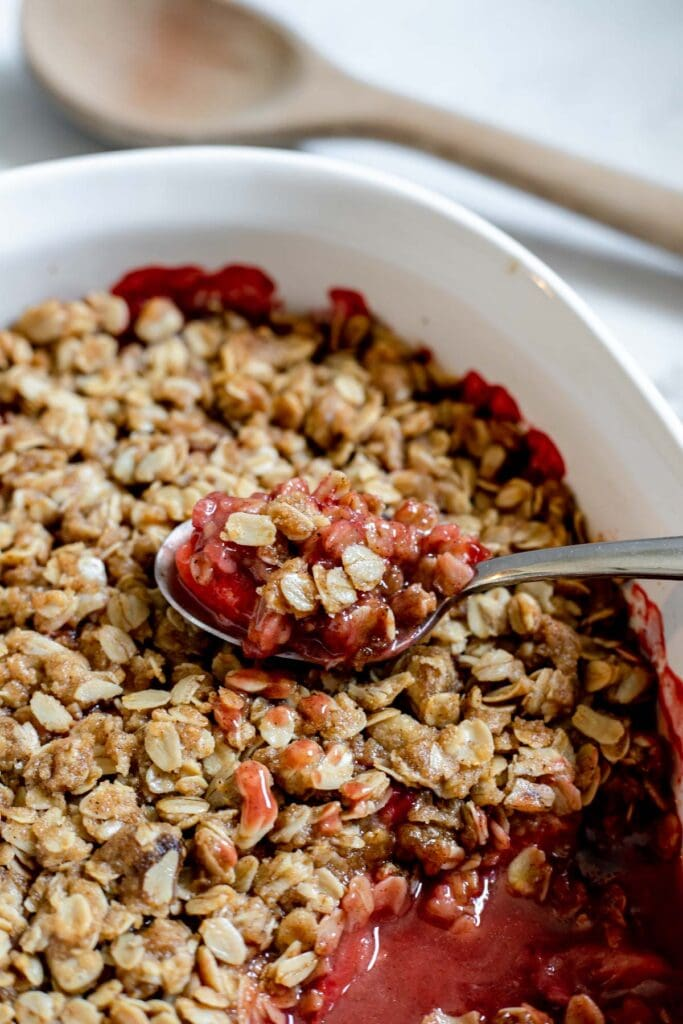 Spoonful of strawberry cardamom crisp resting on top of the rest of the container