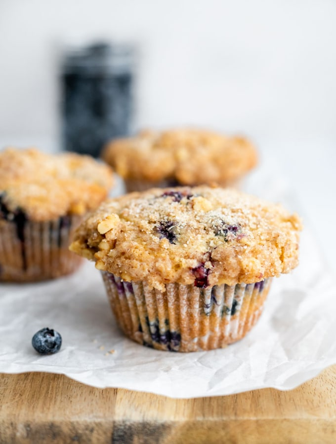 Three blueberry muffins on a cutting board in front of blueberries
